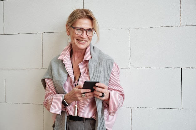 Portret van gelukkige succesvolle rijpe onderneemster met sweater op schouders die moderne telefoon met behulp van