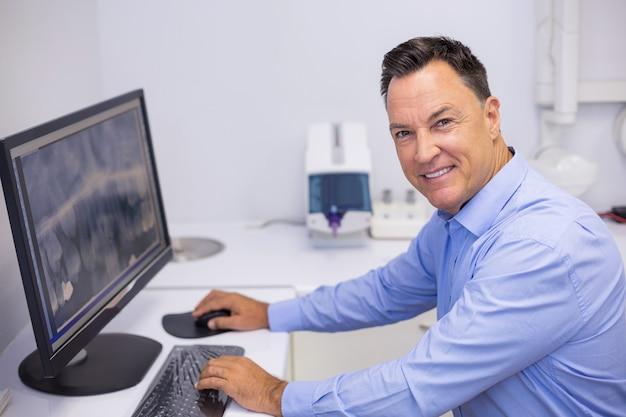 Portret van gelukkige tandarts die x-ray rapport over computer onderzoekt