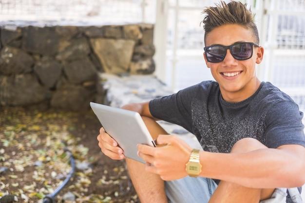 Portret van gelukkige tiener in zonnebril, met behulp van digitale tablet zittend op de grensmuur naast het hek. glimlachende zelfverzekerde jongen die digitale tablet bedient terwijl hij naar de camera kijkt