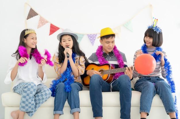 Portret van gelukkige tienerjaren die de gitaar spelen omringd door vrienden