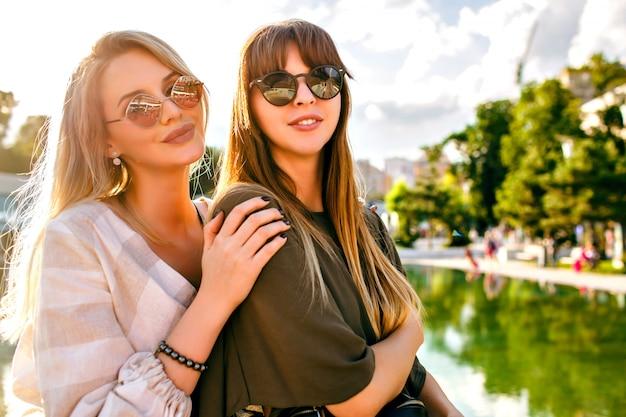 Portret van gelukkige twee zussen beste vrienden vrouw, tijd doorbrengen in stadspark, trendy kleding en zonnebril dragen