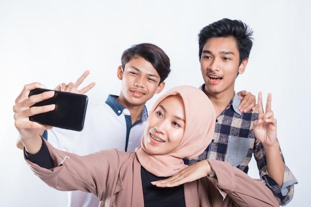 Portret van gelukkige universitaire jongeren die een selfie met de mobiel op een geïsoleerd wit nemen