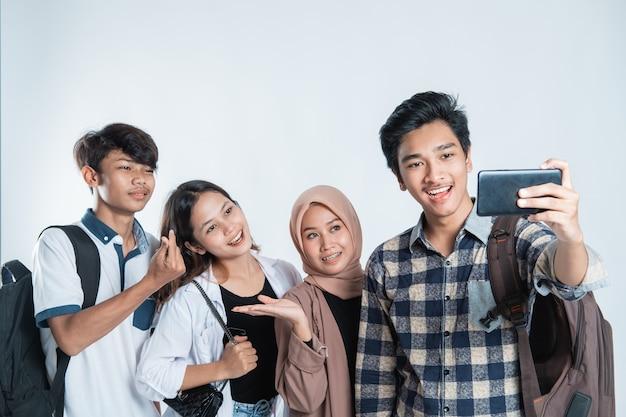 Portret van gelukkige universitaire jongeren die een zak dragen en een selfie met de mobiel op een geïsoleerd wit nemen