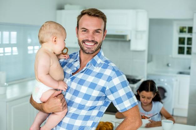 Portret van gelukkige vader dragende zoon in keuken