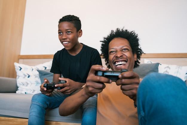 Portret van gelukkige vader en zoon in banklaag zitten en thuis consolevideospelletjes spelen