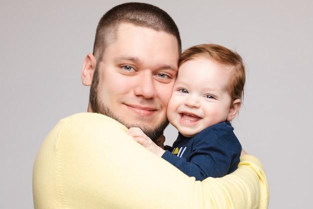 Portret van gelukkige vader poseren met mooie glimlachend kind.