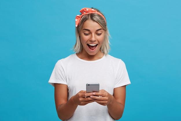Portret van gelukkige verbaasde blonde jonge vrouw met geopende mond draagt een wit t-shirt