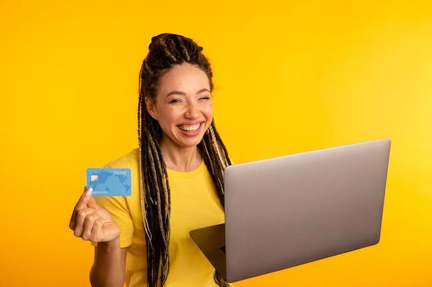 Portret van gelukkige verlaten jonge dame met laptop en creditcard die over de gele studio wordt geïsoleerd.
