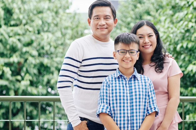 Portret van gelukkige vietnamese familie met preteen kind dat zich buiten bevindt en kijkt