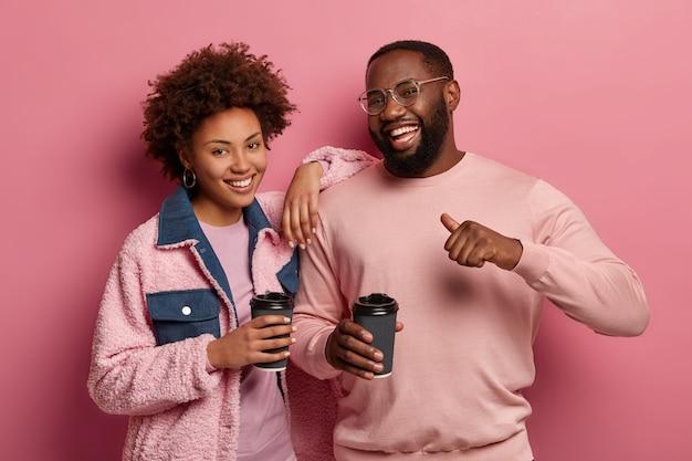 Portret van gelukkige vriendelijke vrouw en man drinken samen koffie, staan dicht bij elkaar, blij mannetje wijst duim naar zichzelf, voelt zich trots