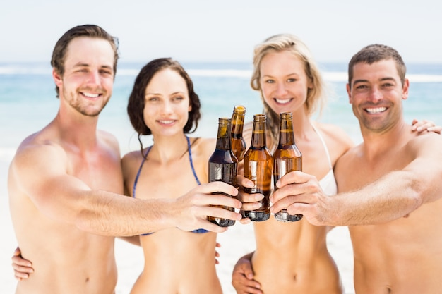 Portret van gelukkige vrienden die bierflessen op het strand roosteren