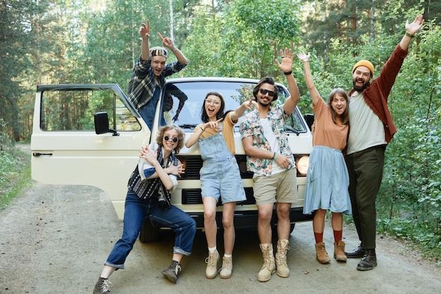 Portret van gelukkige vrienden die naar de camera glimlachen en zwaaien in de buurt van het busje buitenshuis