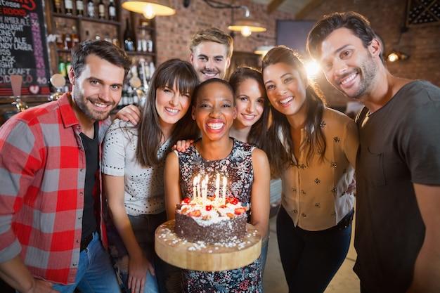 Portret van gelukkige vrienden die verjaardagstaart houden