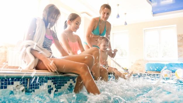 Portret van gelukkige vrolijke familie zittend aan het zwembad en opspattend water met voeten. familie spelen en plezier maken bij het zwembad