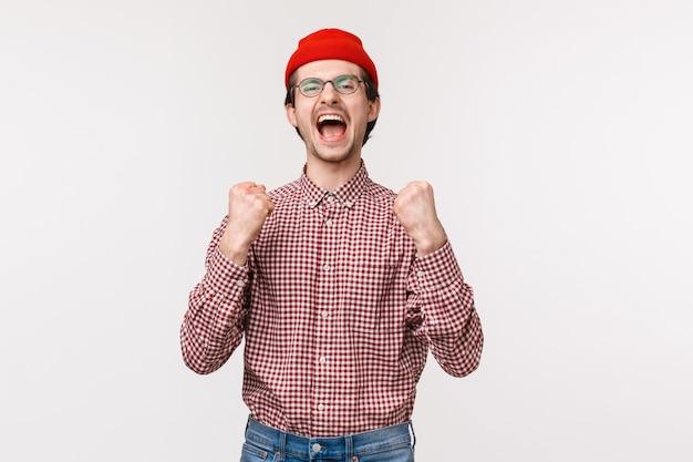 Portret van gelukkige vrolijke jonge man geplaatst weddenschap en prijs winnen, wroeten voor team kijken naar sportwedstrijd, triomfantelijk schreeuwen en vuistpomp als overwinning vieren, kampioen worden,