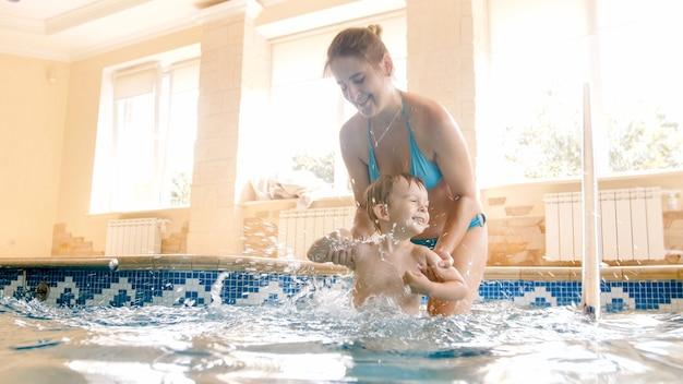 Portret van gelukkige vrolijke jonge mothet met 3 jaar oude peuterjongen die in het zwembad thuis speelt. kind leren zwemmen met ouder. familie plezier in de zomer
