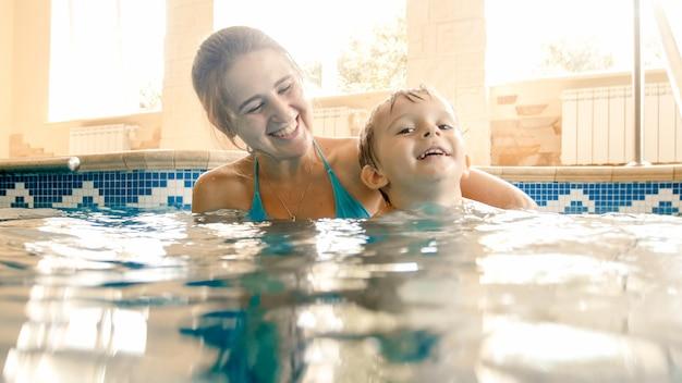 Portret van gelukkige vrolijke jonge mothet met 3 jaar oude peuterjongen die in het zwembad thuis speelt. kind leren zwemmen met ouder. familie plezier in de zomer Premium Foto