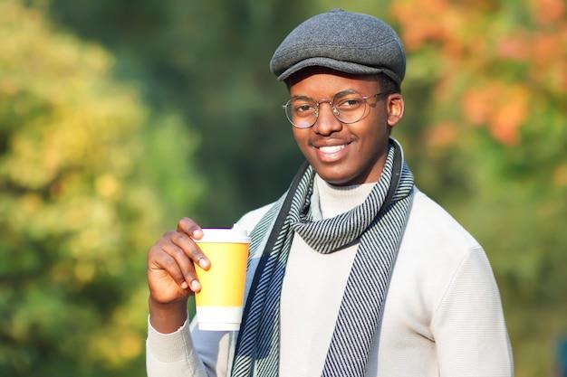 Portret van gelukkige vrolijke positieve zwarte man, jonge afro-amerikaanse etnische man lacht, drinkt koffie of thee in plastic of papieren beker in glazen, muts en sjaal in gouden herfst zonnig park