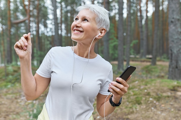 Portret van gelukkige vrolijke volwassen vrouw in wit t-shirt en oortelefoons met plezier buitenshuis