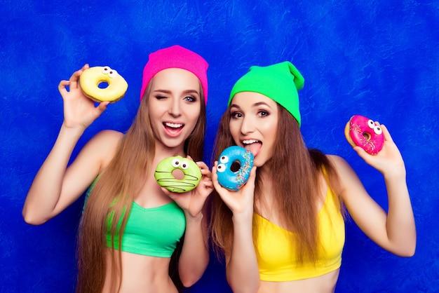 Portret van gelukkige vrolijke vrouwen die donuts gaan eten