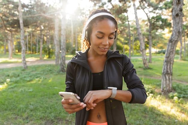 Portret van gelukkige vrouw 20s dragen zwarte trainingspak en koptelefoon, polshorloge kijken tijdens het wandelen door groen park