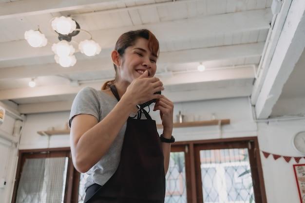 Portret van gelukkige vrouw café- en restauranteigenaar met gezichtsmasker