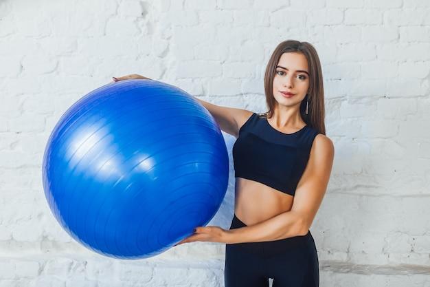 Portret van gelukkige vrouw die blauwe oefeningsbal houdt bij witte geschiktheidsstudio.