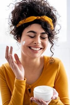 Portret van gelukkige vrouw die en met moisturizer lacht speelt