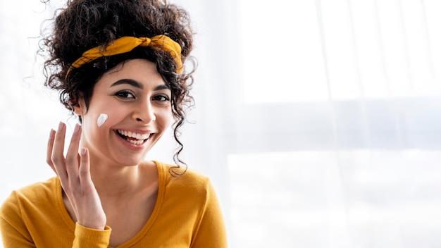 Portret van gelukkige vrouw die en met vochtinbrengende crème met exemplaarruimte lacht speelt