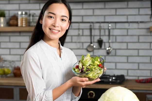 Portret van gelukkige vrouw die verse gemengde groentesalade in keuken toont