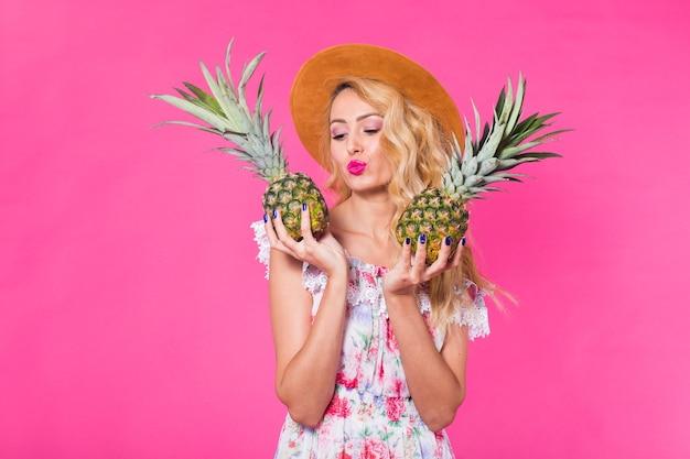 Portret van gelukkige vrouw en ananas over roze muur.