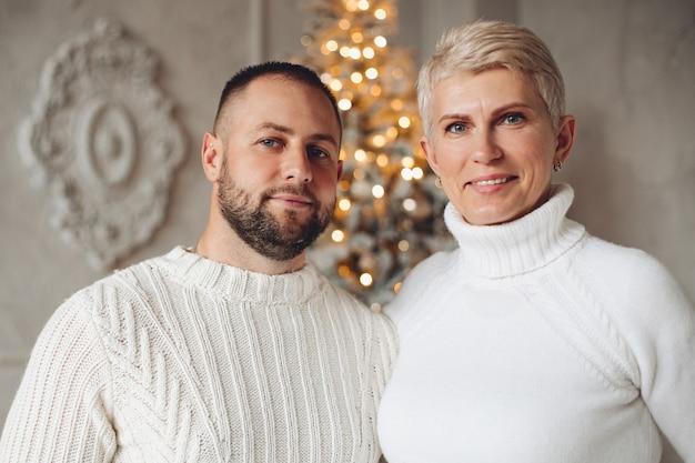 Portret van gelukkige vrouw en man kijken naar camera met kerstboom op de achtergrond