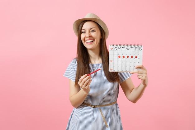 Portret van gelukkige vrouw in blauwe jurk, hoed met rood potlood, vrouwelijke periodenkalender voor het controleren van menstruatiedagen geïsoleerd op roze achtergrond. medische gezondheidszorg, gynaecologisch concept. ruimte kopiëren