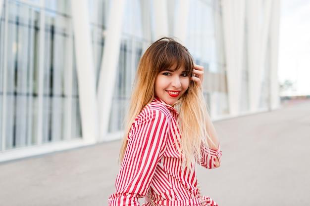 Portret van gelukkige vrouw in rode jurk poseren op straat close-up.