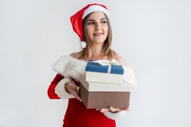 Portret van gelukkige vrouw in santa claus-uitrusting met hoop van dozen