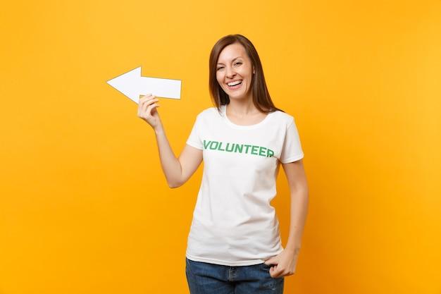 Portret van gelukkige vrouw in wit t-shirt geschreven inscriptie groene titel vrijwilliger houd pijl opzij geïsoleerd op gele achtergrond. vrijwillige gratis hulp, liefdadigheidswerkconcept.