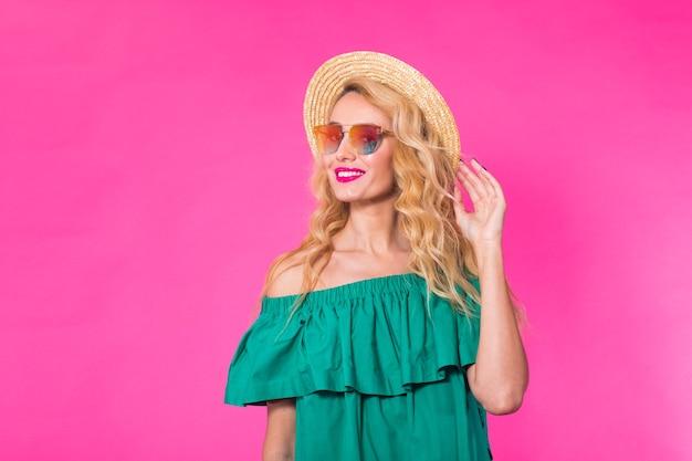 Portret van gelukkige vrouw in zonnebril op roze muur