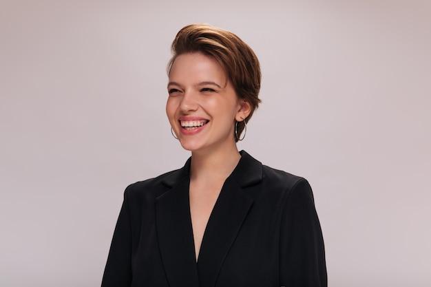 Portret van gelukkige vrouw in zwarte jas. gelukkig kortharig meisje in een donker pak glimlacht wijd en oprecht op geïsoleerde achtergrond