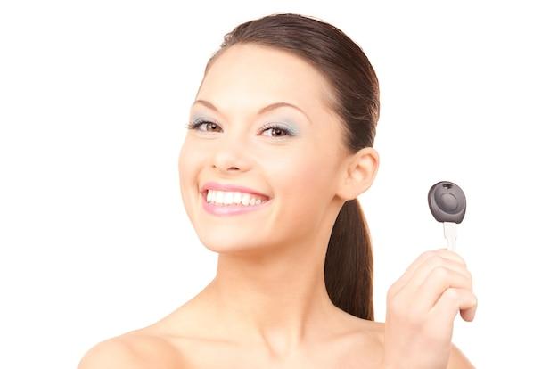 Portret van gelukkige vrouw met autosleutel over witte muur