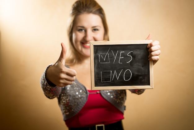 Portret van gelukkige vrouw met duim omhoog en schoolbord met woord