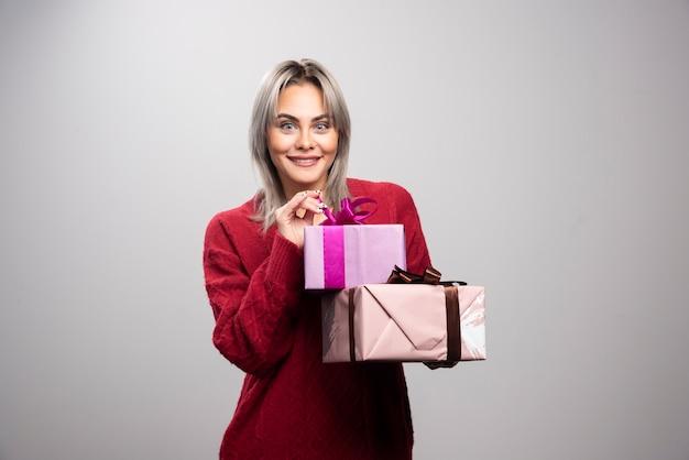 Portret van gelukkige vrouw met geschenkdozen poseren.