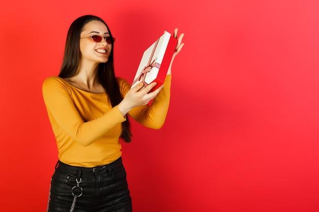 Portret van gelukkige vrouw met huidige doos geïsoleerd op rode achtergrond.