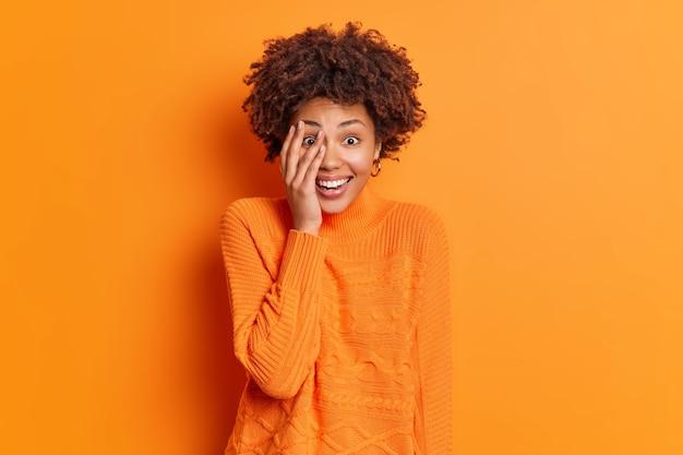 Portret van gelukkige vrouw met krullend borstelig haar geniet van vrije tijd maakt gezicht palm glimlacht in grote lijnen goed humeur draagt casual heldere trui geïsoleerd over oranje muur