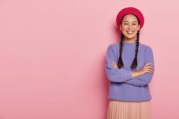 Portret van gelukkige vrouw met oosterse uitstraling, houdt de handen gekruist over de borst, draagt rode baret, paarse trui en rok, poseert tegen roze muur, heeft een enthousiaste blik