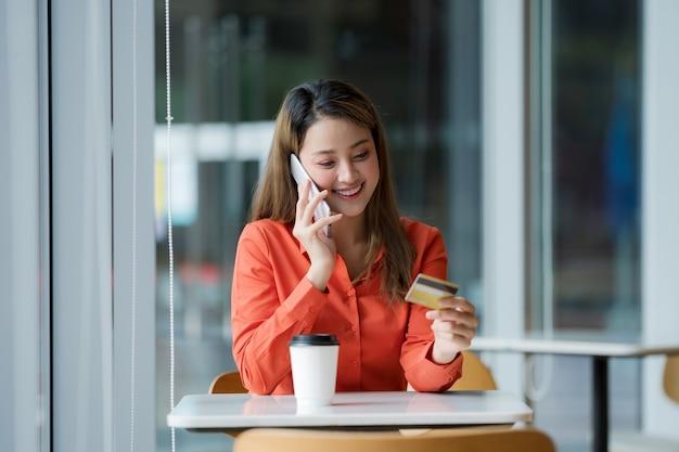 Portret van gelukkige vrouw met slimme telefoon met creditcard en lachend gezicht in creatieve kantoor of café in het winkelcentrum