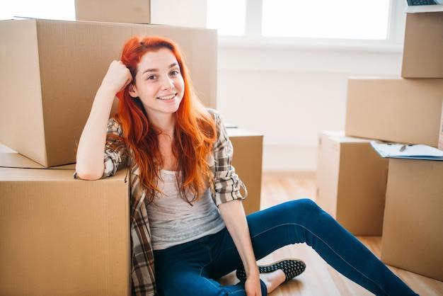 Portret van gelukkige vrouw onder kartonnen dozen, housewarming. verhuizing naar nieuw huis