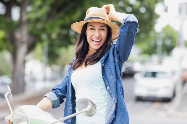 Portret van gelukkige vrouw op bromfiets