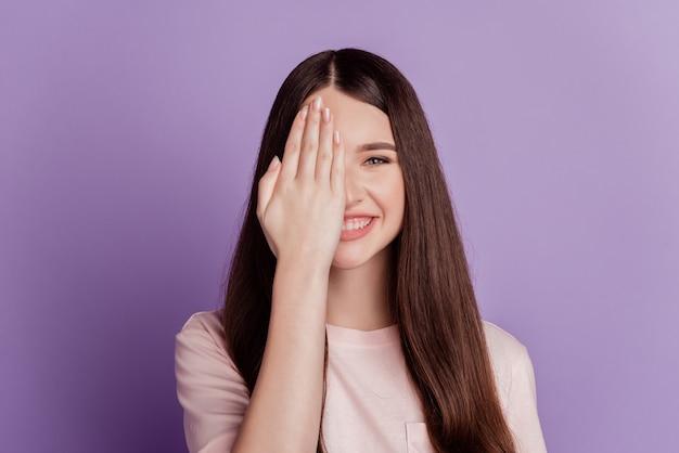 Portret van gelukkige vrouw palm cover oog horloge toothy glimlach geïsoleerd op paarse achtergrond