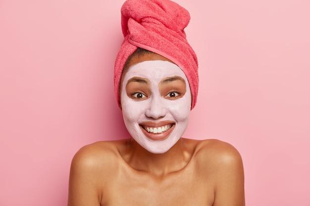 Portret van gelukkige vrouw past klei voedend gezichtsmasker toe, heeft blije uitdrukking, is in goed humeur, geniet van verjongingsbehandeling, draagt roze handdoek op nat haar