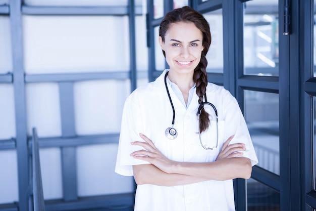 Portret van gelukkige vrouwelijke arts die zich met die wapens bevinden in het ziekenhuis worden gekruist